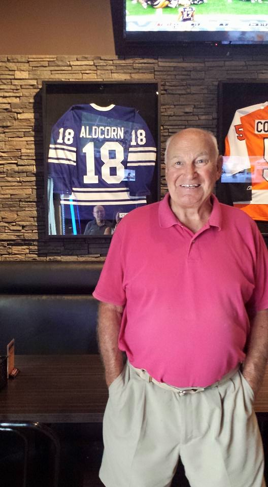 Gary Aldorn standing in front of his jersey at Overtime.
